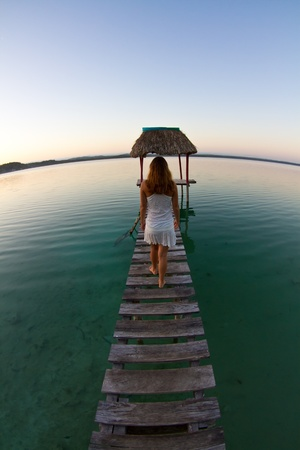 A girl dressed in white walks away from the camera, along a jettyon lake Peten.