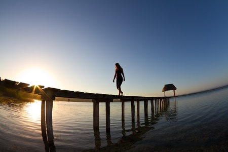 self discovery: Sunrise over lake with young girl on jetty