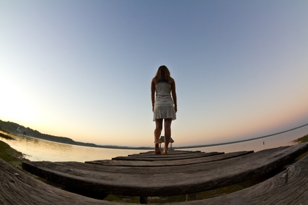 A girl dressed in white walks away from the camera, along a jetty on lake Peten. Stock Photo