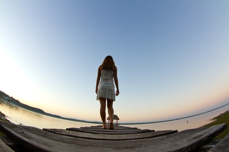 A girl dressed in white walks away from the camera, along a jetty on lake Peten. Stock Photo - 9055852