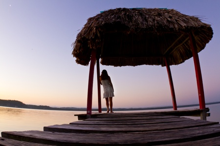 A young woman reflects upon the sunrise over the lake. Stock Photo - 9115853