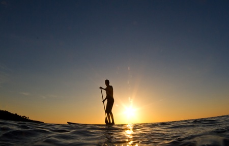 A young man paddles his surfboard in to shore at sunset Stock Photo