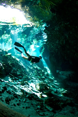 free diver: A young woman free dives into a Cenote