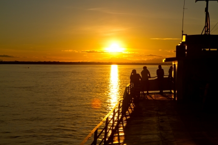 Some friends ejoy the last light on the Amazon river. Stock Photo - 10024074
