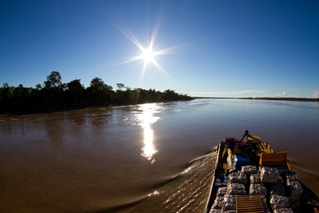 peru amazon: A large cargo ship moves slowly up the river Amazon to unload its cargo.