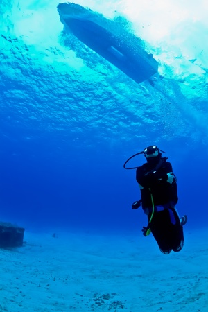A young female scuba diver looks up as a speeding boat zooms over head on a dive in Mexico.