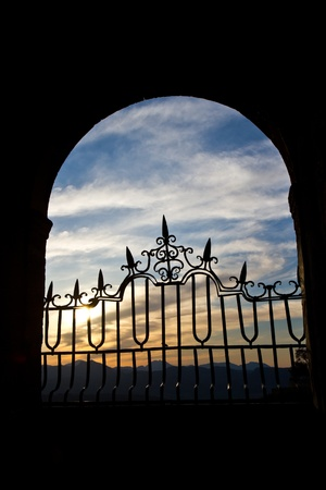 country side: The sun sets over the Spanish mountains through an old stone arch in Ronda.