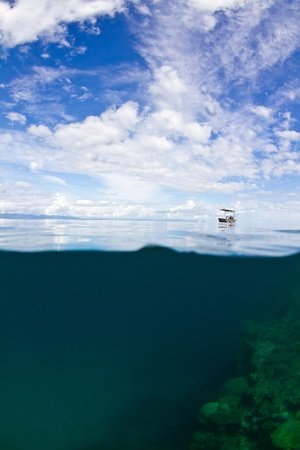 pristine corals: A lonely small boat is moored up at the great barrier reef in Australia. Stock Photo