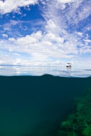 pristine coral reef: Una barca solitaria piccolo pontile alla grande barriera corallina in Australia.