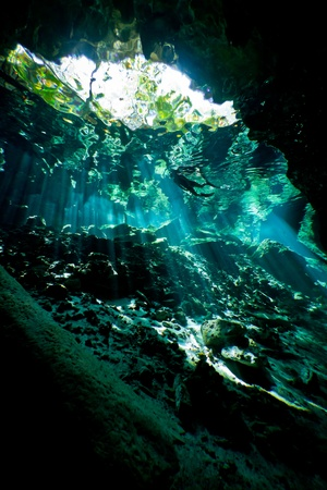 Silhouette of a lone female snorkeller from inside an underwater cave system in mexico.