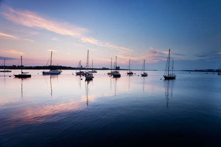 Pinks and blues of sunrise sky over boats in Boston Harbor photo