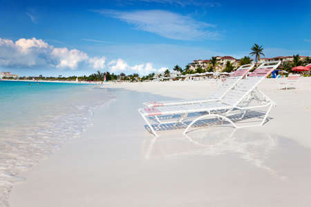 Beach chaises at waters edge on the soft white sands of Grace Bay Beach, Turks & Caicos photo