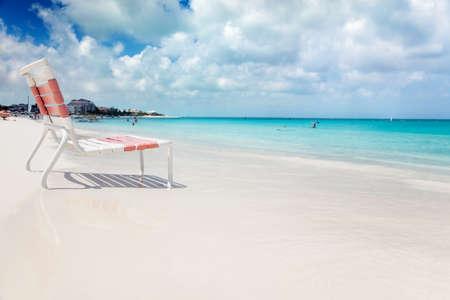turks: Silla baja playa en el borde de las tranquilas aguas color turquesas de Grace Bay, los turcos & Caicos Foto de archivo