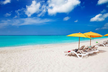 Vivid blue of sky and sea with the white sands of Grace Bay Beach, Turks & Caicos, and bright yellow beach umbrellas photo