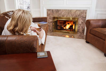 Woman relaxing by a cozy fire Stock Photo - 9692093