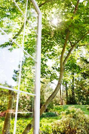 ventana abierta: Ventana abierta al jard�n de verano soleado,