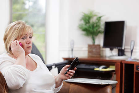 Mature woman talks on one phone as a call comes in on another while working from a home office Stock Photo - 9692091