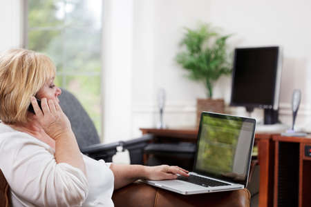 Mature woman on the phone with laptop in home office Stock Photo - 9692086