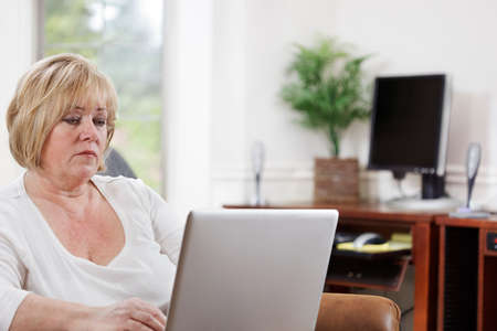 Mature woman typing on a laptop in her home office Stock Photo - 9692089