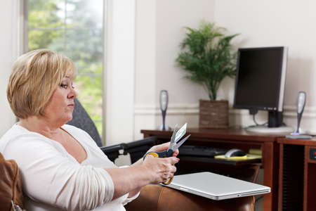 Mature woman determinedly cuts up her credit card - no more online shopping Stock Photo - 9736692