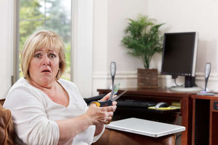 Mature woman is utterly dismayed at having to cut up her credit card photo