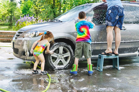 Brother & sister help Dad with washing a car in the driveway Stock Photo