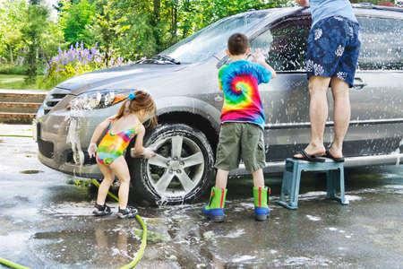 ni�os ayudando: Hermano & hermana ayudar a pap� con un coche en el camino de lavado Foto de archivo