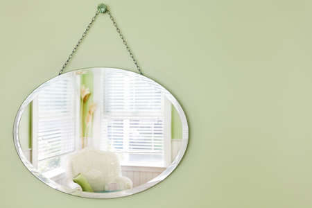 sitting area: Oval mirror hanging on the wall in a summery beach house sitting area