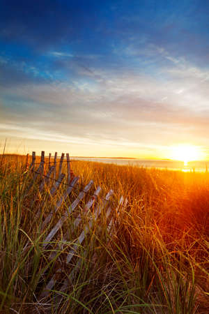 Sun rises over the dunes and a collapsing wooden fence on a Maine beach photo