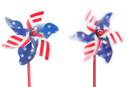 Two stars & stripes pinwheels, one stationary, one spinning, isolated photo