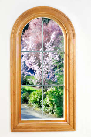 round window: Round top window with a view of spring flowering trees in sunshine
