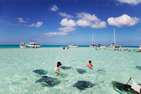 cayman islands: Brother & sister enjoy playing with the stingrays at the sandbar off Grand Cayman