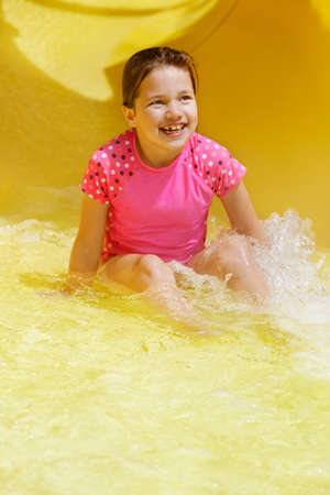 exits: Young girl looks up as she exits a water slide Stock Photo