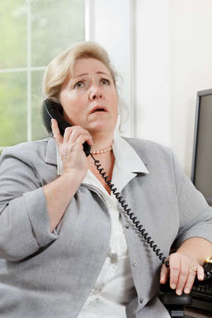 exasperation: Mature woman rolls eyes up in exasperation while talking on the phone