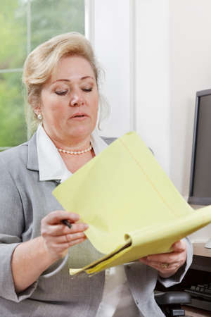 legal pad: Mature woman reviewing notes on a yellow legal pad Stock Photo