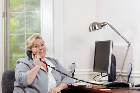 woman on phone: Mature woman smiles as she talks on the phone