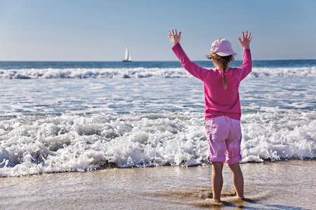 Young girl holds up hands as wave approaches her photo