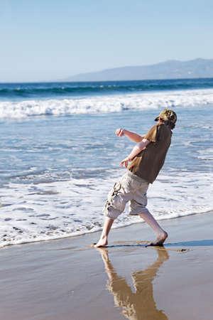 skimming: Adolescente skimming piedras en la playa Foto de archivo