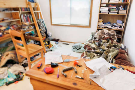 untidy: Teenage boys messy room. Tilt shift lens, with focus on pillow & comforter Stock Photo