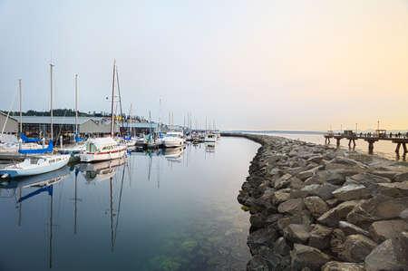 edmonds: Hazy summer sun going down over the marina in Edmonds Stock Photo