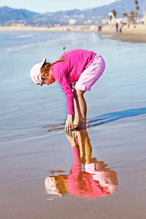 Young girl and her reflection playing on the beach near the water photo