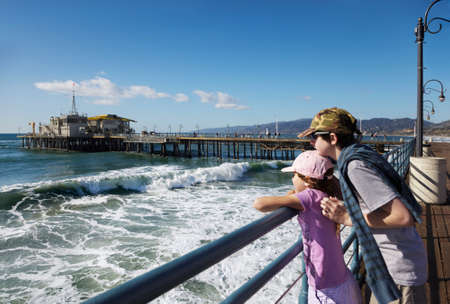 Brother holds his sister as they watch the waves from the end of the pier photo
