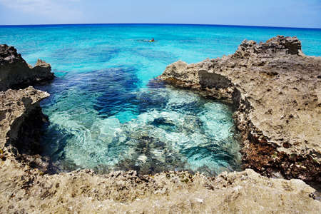Man explores the reef off the rocky (Ironshore formation) areas of Smith Cove, Grand Cayman. Slight curve to the horizon photo