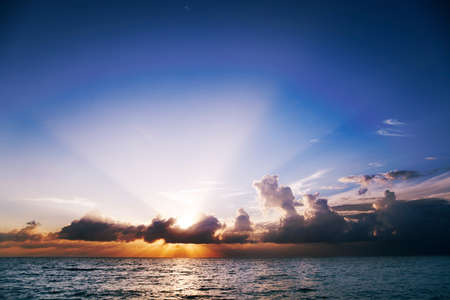 mile: Suns rays fan out from clouds at sunset over Seven Mile Beach, Grand Cayman Stock Photo