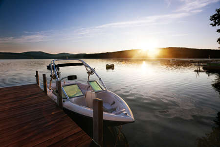 wooden boat: Boat docked on a calm lake in morning light