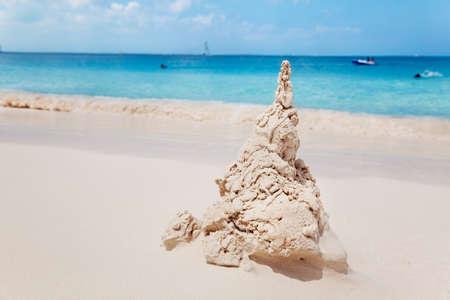 turks: Ni�a relojes de agua como las ondas comienzan a erosionar su castillo de arena, la playa de la Bah�a de gracia, turcos & Caicos Foto de archivo