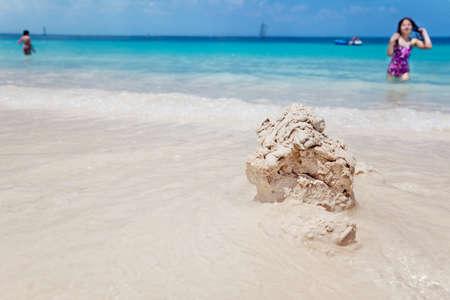 turks: Ni�a camina a inspeccionar su castillo de arena arrastrada por las olas de Grace Bay, los turcos & Caicos