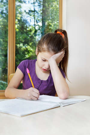 glum: Young girl looks very glum as she works on her Science Fair notes Stock Photo