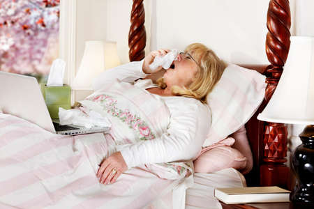 Mature woman unwell, and  trying to work from home as she lies in bed and sneezes photo