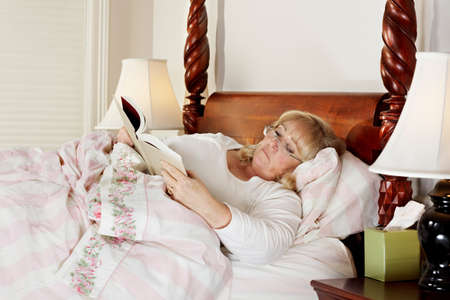 Mature woman reads a book while lying in bed photo